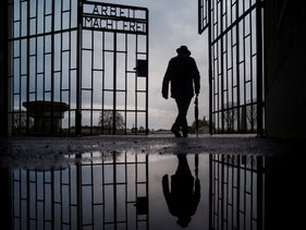 a man walks through the gate of the Sachsenhausen Nazi death camp with the phrase 'Arbeit macht frei' (work sets you free) during International Holocaust Remembrance Day in Oranienburg, about 30 kilometers (18 miles), north of Berlin, Germany.