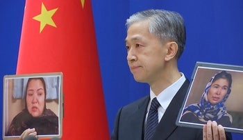 Chinese Foreign Ministry spokesman Wang Wenbin holds pictures while speaking during a news conference in Beijing, China.