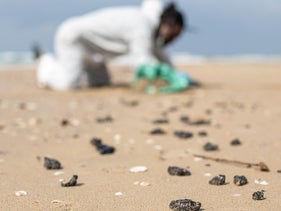A man cleans newly washed up black tar from a beach north of Netanya following an unreported oil spill.