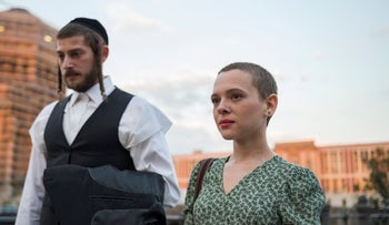 """Shira Haas and Amit Rahav, left, and in a scene from """"Unorthodox,"""" in 2014."""
