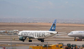 A Frontier Airlines jetliner waits for a United Airlines jetliner to pass on a taxiway outside the terminal of Denver International Airport early Thursday
