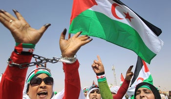 Women refugees from Western Sahara wave their unofficial flag during a military parade, last month.