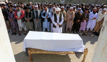 Afghan men pray in front of the coffin of one of three female media workers who were shot and killed by unknown gunmen, in Jalalabad, Afghanistan.