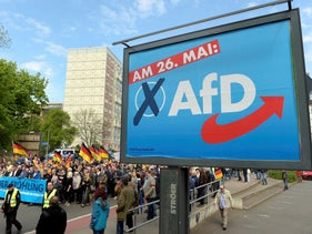 AfD supporters walkin along a party elections poster in Erfurt, Germany.
