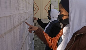 Palestinian women look for their names on the electoral roll at a school in Gaza City ahead of the upcoming Palestinian elections, yesterday.