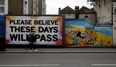 People wearing face masks walking past a billboard in London with a recent work by artist Mark Titchner last year.