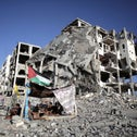 Palestinians sitting outside a destroyed apartment building in Beit Lahiya, Gaza, in 2014.
