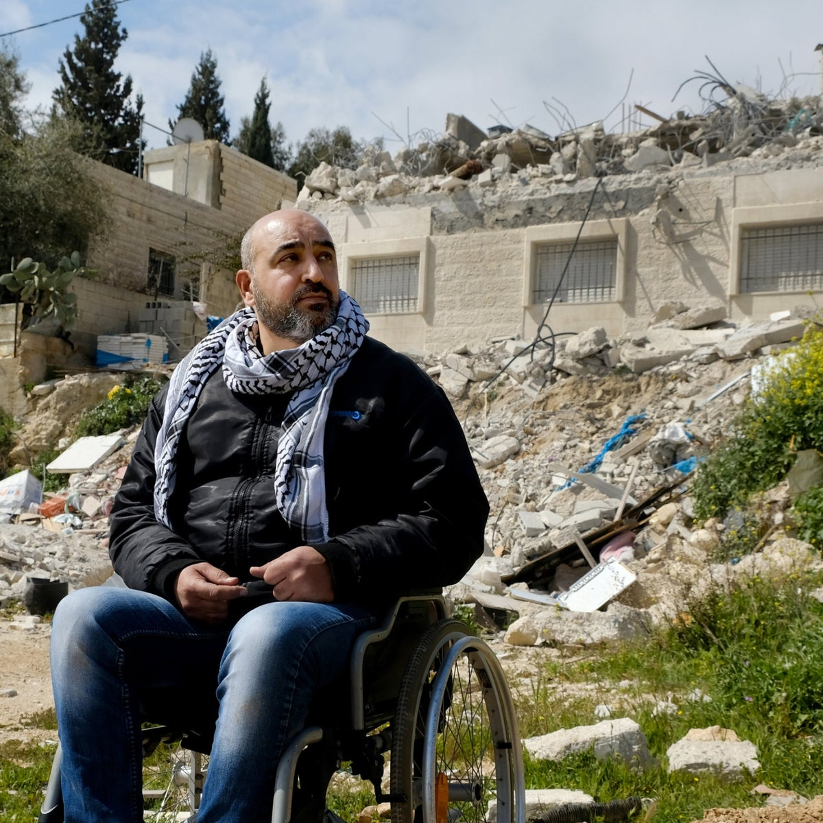 Khatham Abu Riala in front of what used to be his home in Isawiyah.