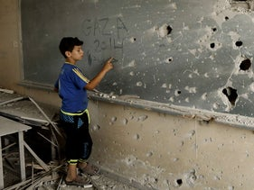 A Palestinian boy writes on a shrapnel riddled backboard in Gaza City during the 2014 war between Israel and Hamas.