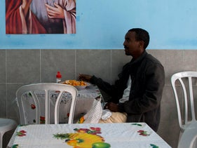 An African migrant sits at a restaurant in Tel Aviv.