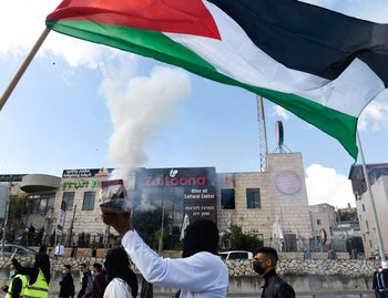 A protester lights a firecracker under a Palestinian flag at today's protests in Umm-al Fahm