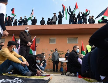 Locals stand on a roof, waving Palestinian flags to protest police brutality in Umm-al Fahm