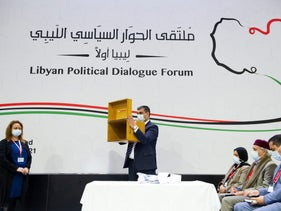 A staff member showing the empty ballot box after delegates voted for a new interim Libyan government at the Libyan Political Dialogue Forum near Geneva last month.