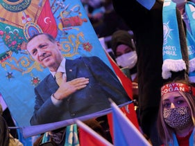 A woman holds a flag with an image of Turkish President Tayyip Erdogan during a local congress of the ruling AK Party in Istanbul, Turkey last month