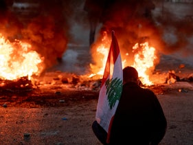 A protester holds a Lebanese national flag as he stands in front of burning that are blocking a main road, during a protest in downtown Beirut last week
