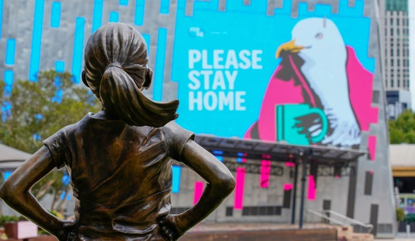"""The Fearless Girl Statue looking at a """"Please stay home"""" sign in Melbourne last month."""