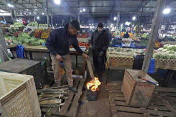 Palestinian vendors burn wood to keep themselves warm amid snowfall at a market in the West bank.