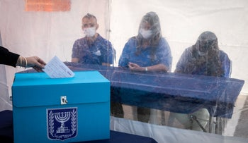 Central Elections Committee workers demonstrate coronavirus precautions that will be used during voting, last month.