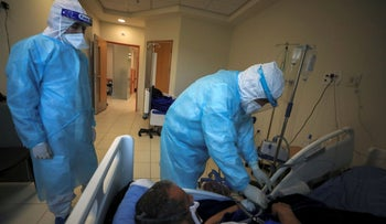 A Palestinian health worker treats a patient infected with the coronavirus at a hospital in Turmus Ayya town in the West Bank, last week.