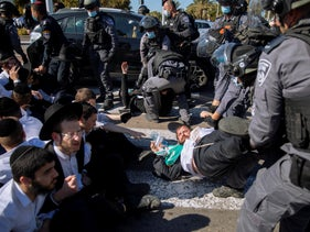 Israeli police officers clash with ultra-Orthodox Jews in Ashdod.
