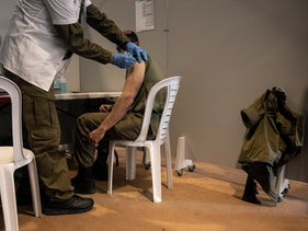 An Israeli soldier gets the coronavirus vaccine on a base in Rishon Lezion, last month.