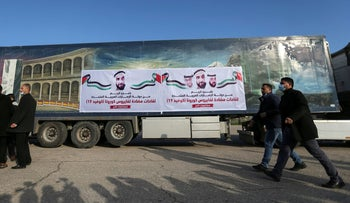 Palestinians walk past a truck carrying a shipment of Russia's Sputnik V vaccine sent by United Arab Emirates, last month