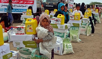 People displaced by conflict receive food aid near the conflict zone in Yemen's western province of Hodeida, last month.