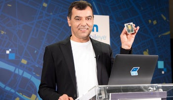 Amnon Shashua holds a chip developed by Mobileye.
