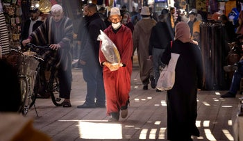 Moroccans walk in the old city of Marrakesh.