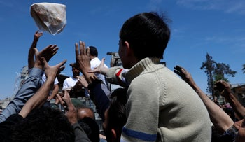 Syrian authorities distribute bread, vegetables and pasta to residents in the town of Douma, near Damascus, Syria.