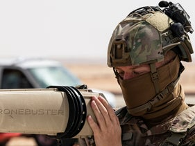 Soldier with the U.S. Air Force trains members of the Royal Saudi Air Force Police Wing how to use equipment to counter drone attacks.