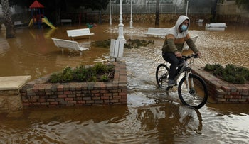 A man cycles in a flooded road in the northern city of Nahariya, two months ago.