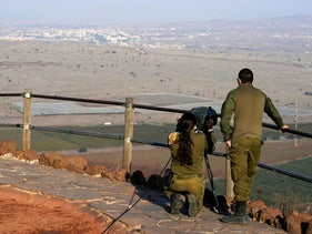 Israeli soldiers look towards Syria across the border from Mount Bental.