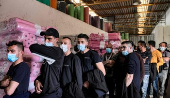 Palestinian laborers working in the Barkan industrial zone queue up to receive their first dose of the Moderna coronavirus vaccine, last week.