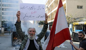 An anti-government demonstrators carries a placard which reads 'The bank is safe, the currency is dead' during a protest in Beirut, on Tuesday.