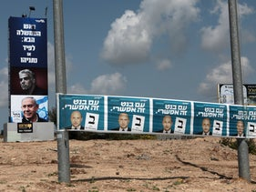 Campaign posters for Prime Minister Benjamin Netanyahu's Likud party and Naftali Bennett's Yamina party yesterday, one week before the election.
