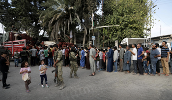 People stand in a queue to get bread in the border town of Tal Abyad, Syria.