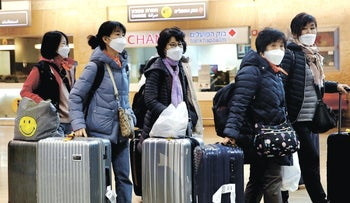 Passengers arriving at Ben-Gurion International Airport wearing face masks to prevent COVID spread.