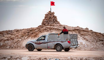 A pickup truck passes by a hilltop manned by Moroccan soldiers on a road between Morocco and Mauritania in Guerguerat located in the Western Sahara, last year.