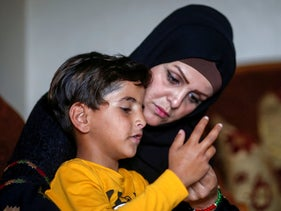 Niveen Gharqoud sits with her son Amir at their home in the central Gaza Strip.