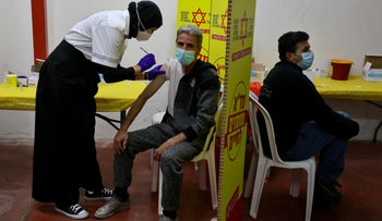A Palestinian man working in the settlement industrial zone of Barkan in the West Bank gets vaccinated.