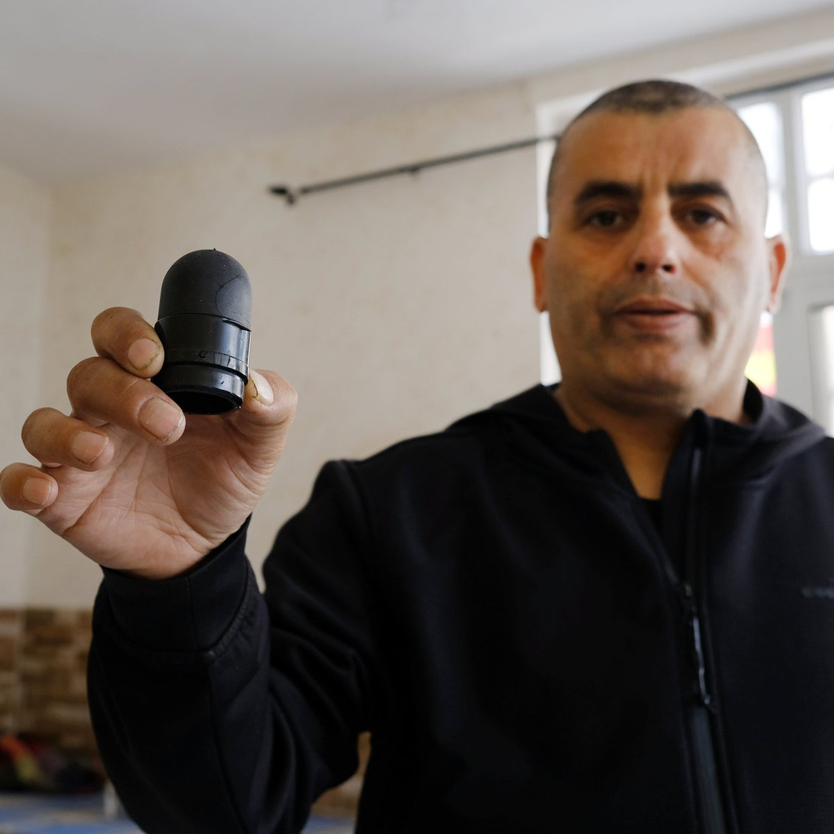 Walid Aabed holding a rubber-tipped bullet that was fired into his parents' home.