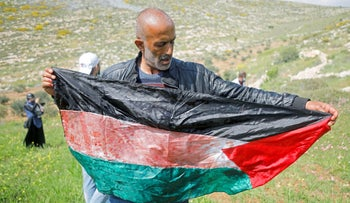 A man holds a Palestinian flag stained with blood of a fatally wounded Palestinian in Beit Dajan, today.