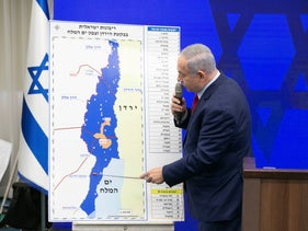 Prime Minister Benjamin Netanyahu points at a map of West Bank settlements in a press briefing to present his annexation plan, ahead of Israel's 2019 election.