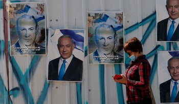 A woman walks past campaign posters of Israeli Prime Minister Benjamin Netanyahu in Israel's southern city of Beersheva
