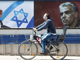 A man bikes past a campaign poster for Prime Minister Benjamin Netanyahu and against one of his challengers, Yair Lapid, last week.