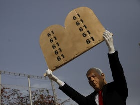An sculpture of Netanyahu erected in Kikar Rabin, he is holding the ten commandments with '61' written as each commandment, the number of seats needed to form a Knesset majority