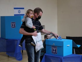 Israeli man casts vote with his child in tow
