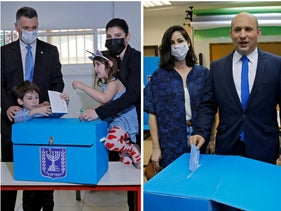 New Hope leader Gideon Sa'ar, left, and Yamina Chairman Naftali Bennett voting on Election Day with their families.