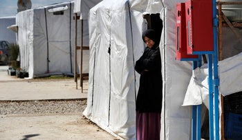 A Syrian displaced woman stands at the entrance of her tent at a refugee camp, in Bar Elias, in eastern Lebanon's Bekaa valley, March.